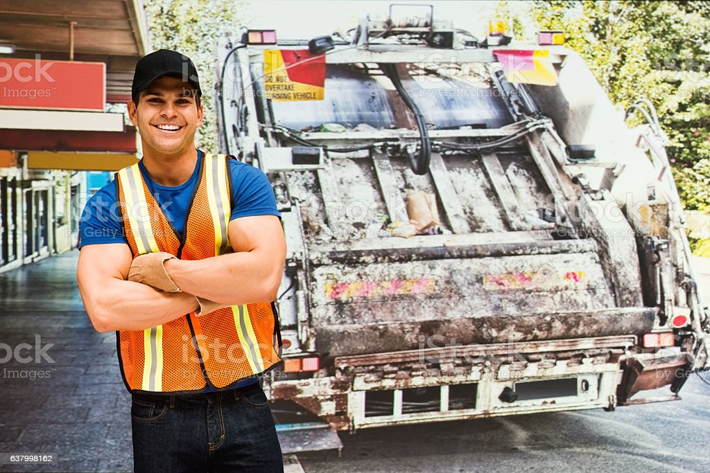 Smiling worker standing in front of garbage can stock photo