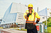 Smiling worker standing in front of power station