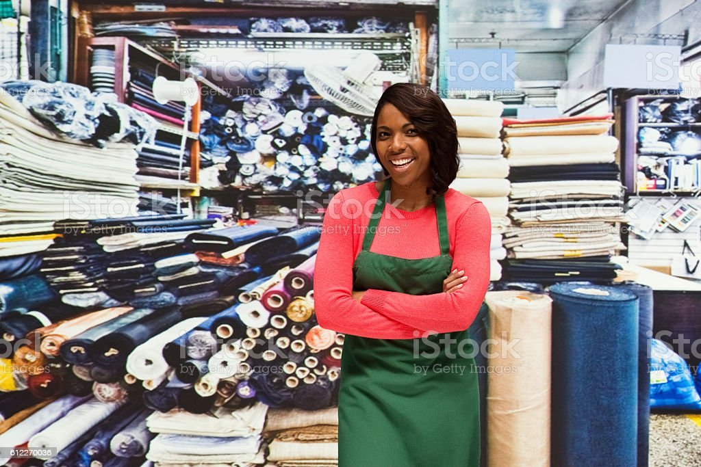 Smiling worker standing in textile industry stock photo