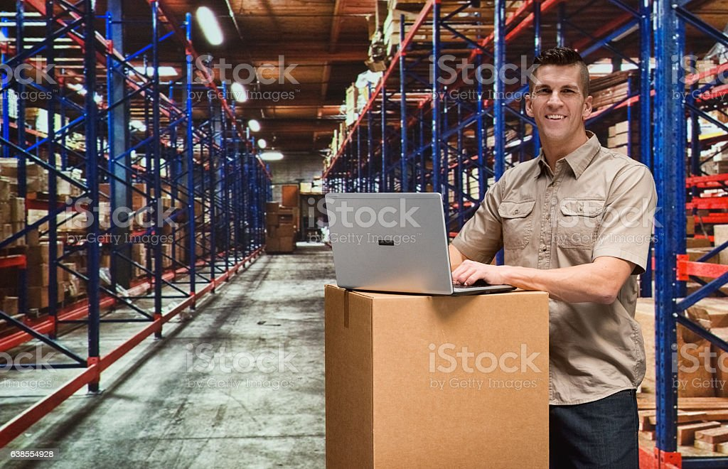 Smiling worker typing on laptop in warehouse stock photo