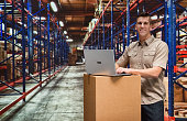 Smiling worker typing on laptop in warehouse