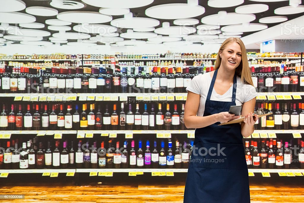 Smiling worker using phone in shopping mall stock photo
