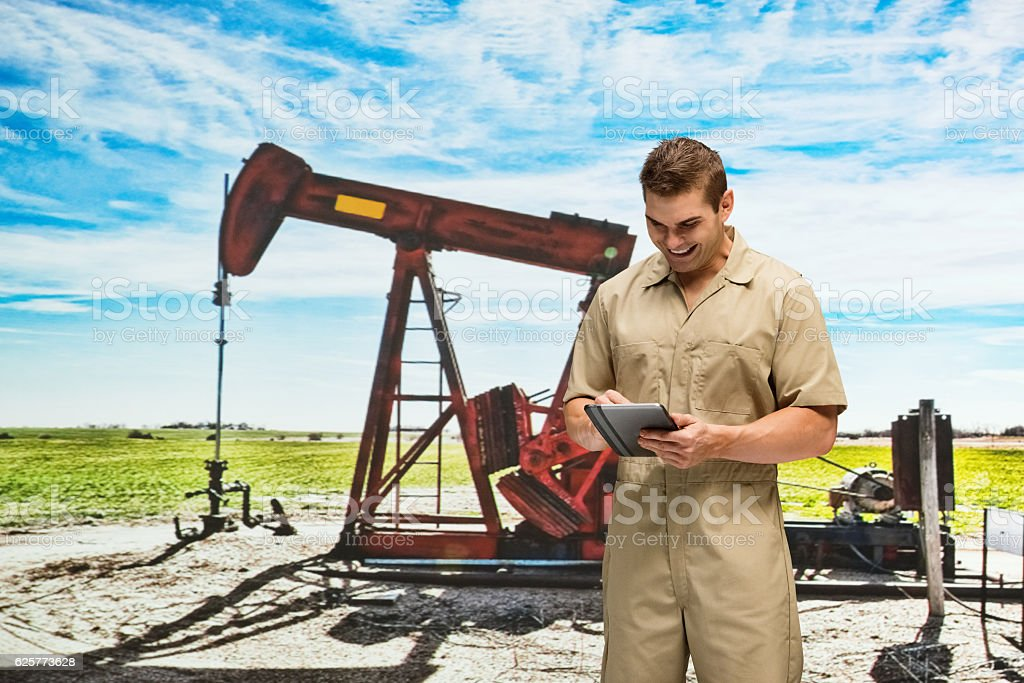 Smiling worker using tablet in front of oil industry stock photo