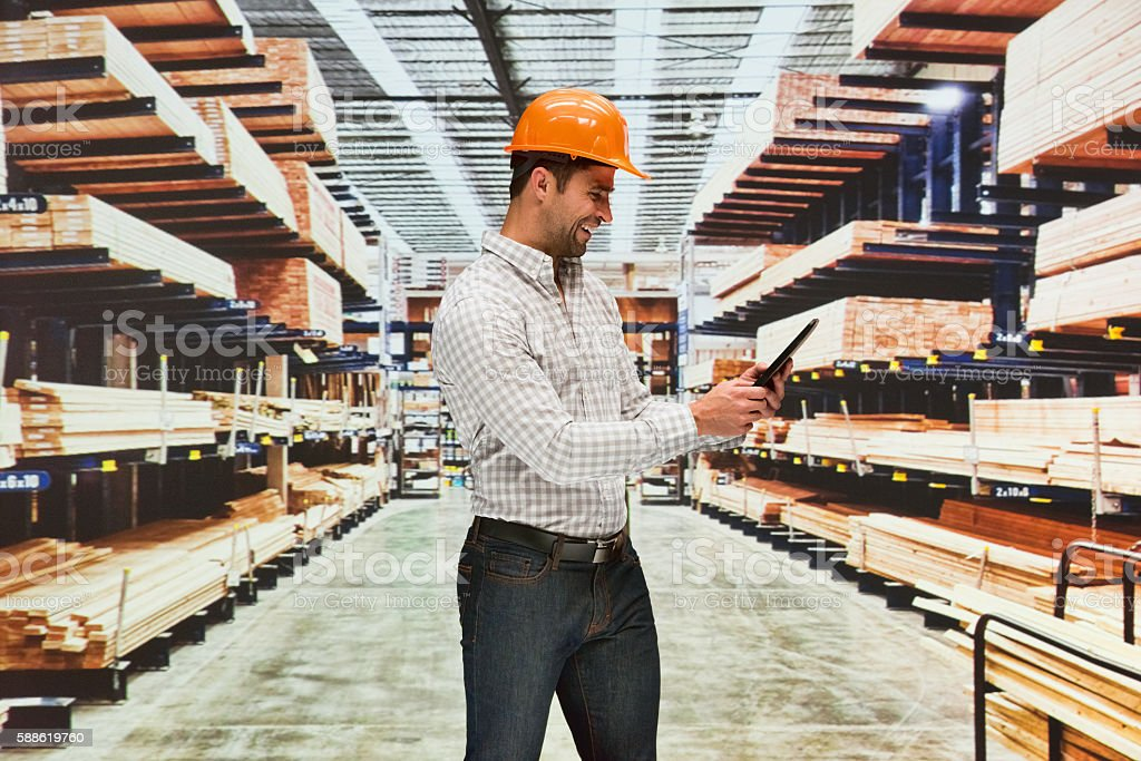 Smiling worker using tablet in warehouse stock photo