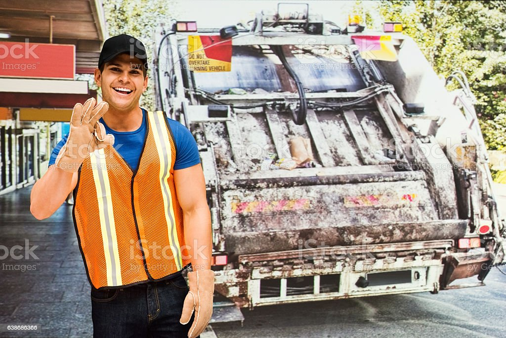 Smiling worker waving hand in front of garbage can stock photo