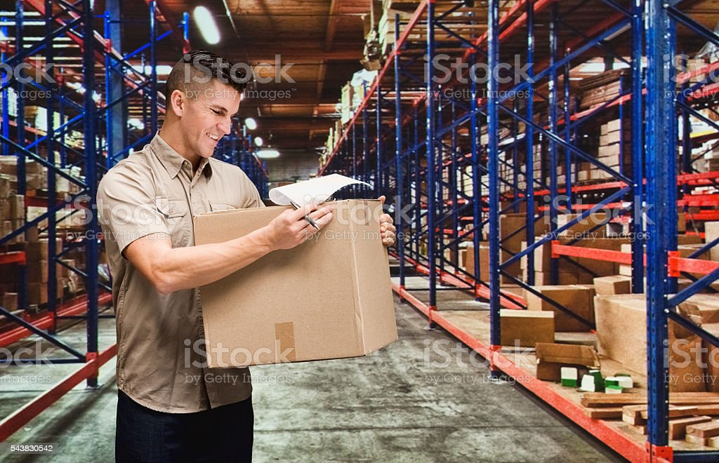 Smiling worker working in warehouse stock photo