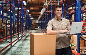 Smiling worker working on laptop in warehouse