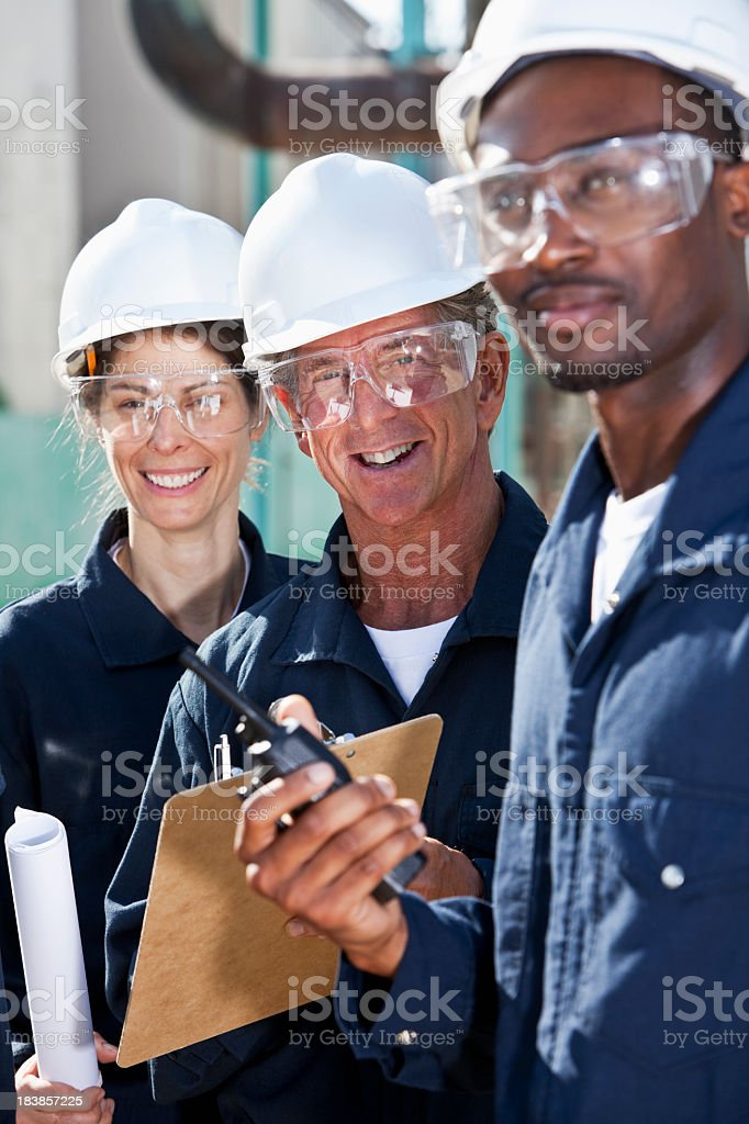Smiling workers with white hard hats royalty-free stock photo