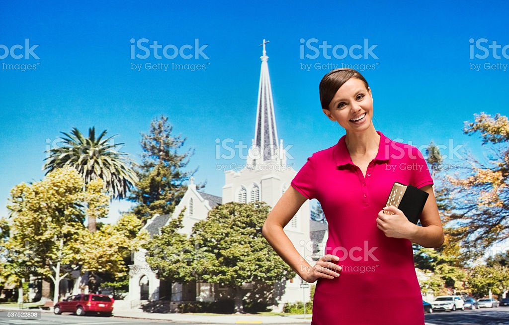 Smiling worshiper in front of church stock photo