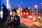 Smiling youn man using smart phone on street at night