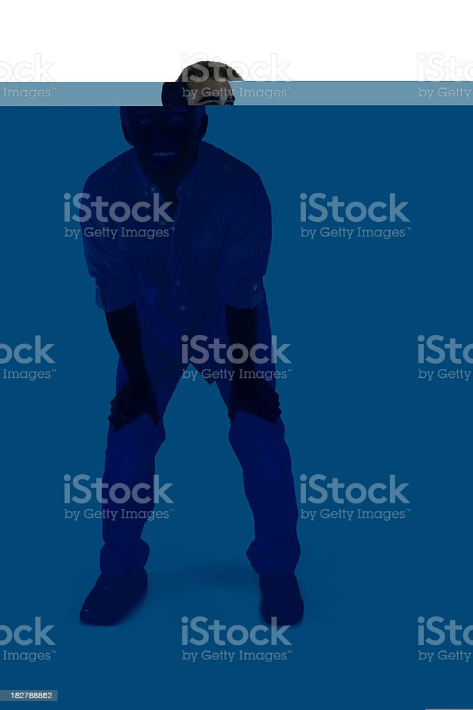 Smiling young adult male leaning foward hands on knees stock photo