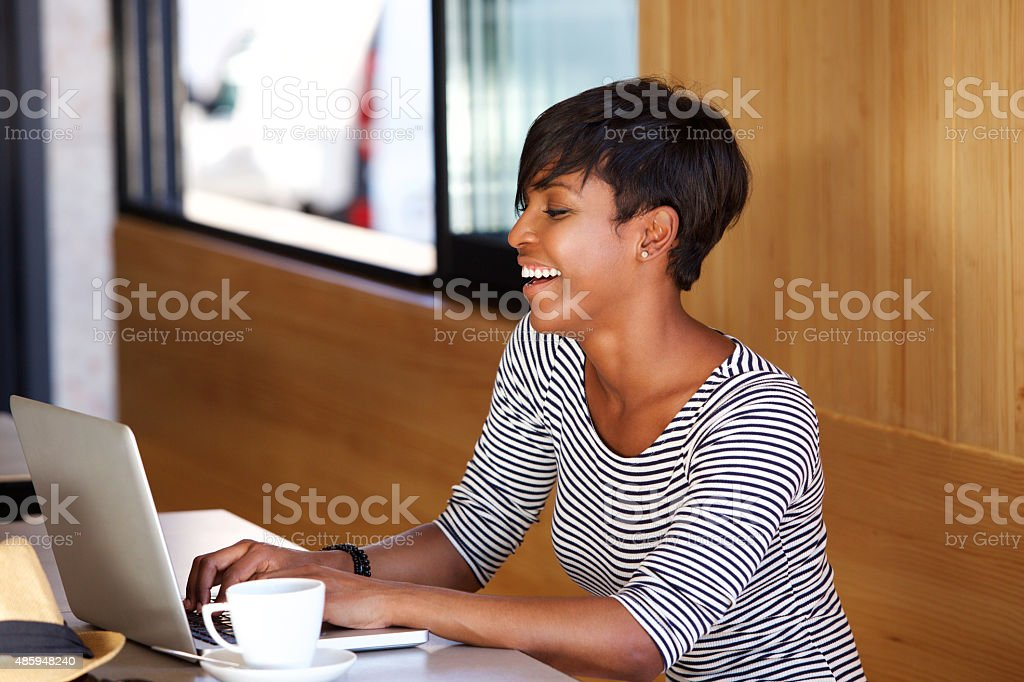 Smiling young african american woman using laptop stock photo