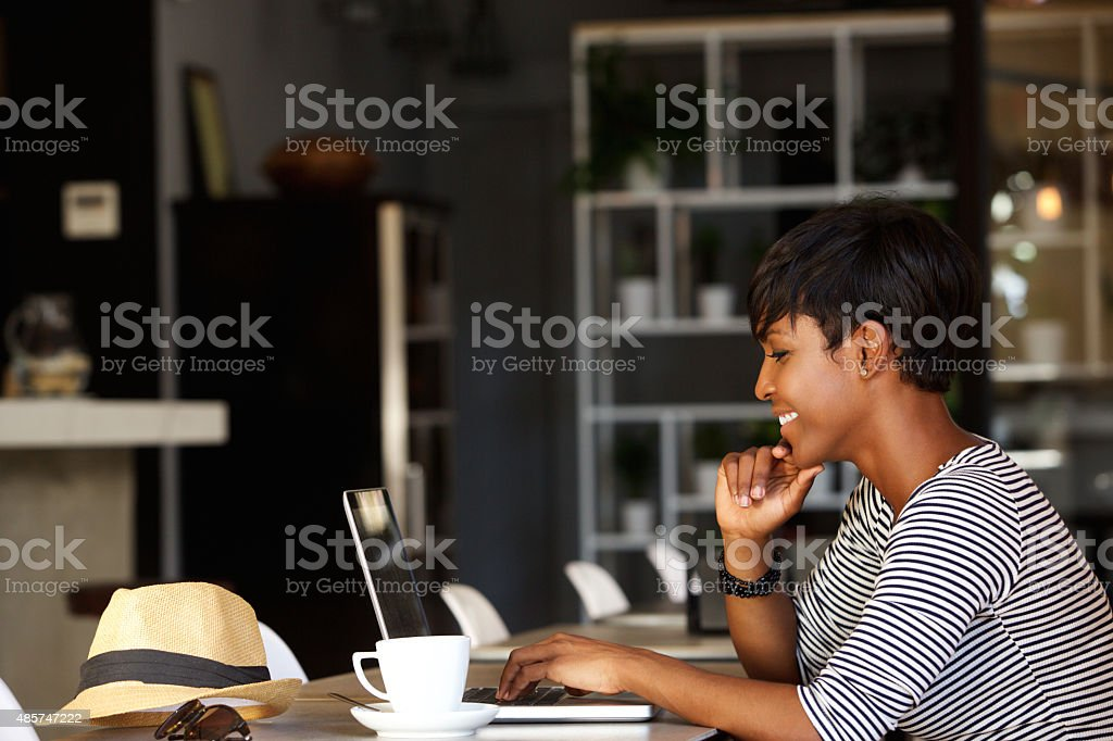 Smiling young african american woman working on laptop stock photo