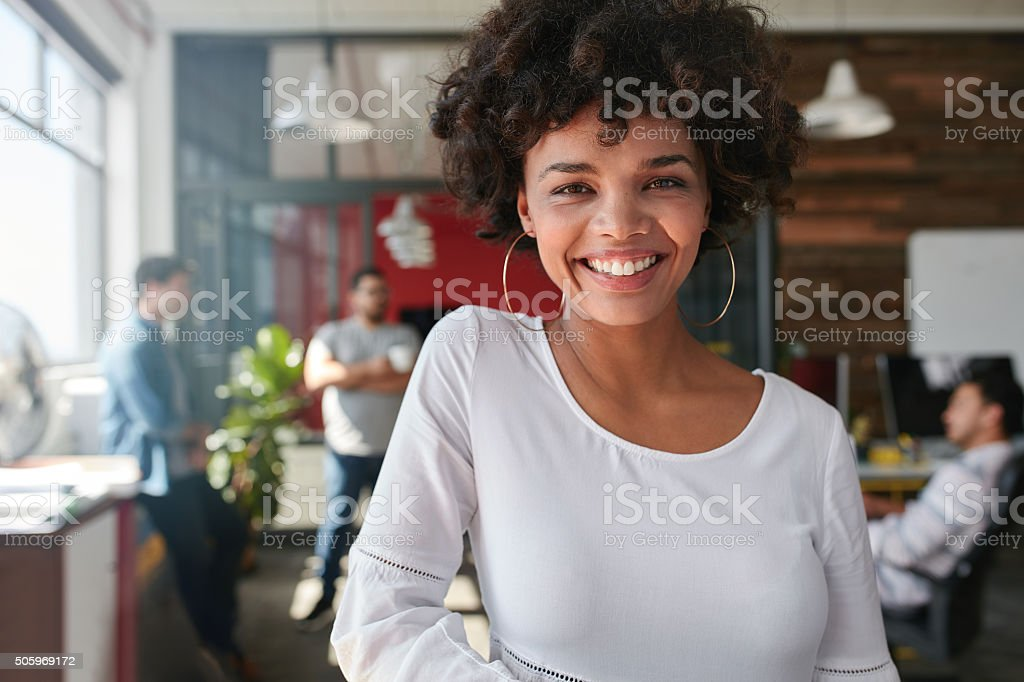 Portrait of smiling young african businesswoman with people in...