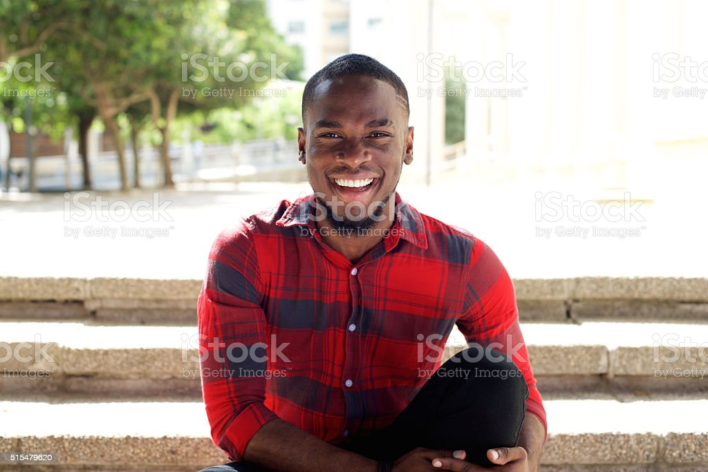 Smiling young african man sitting on steps outdoors stock photo