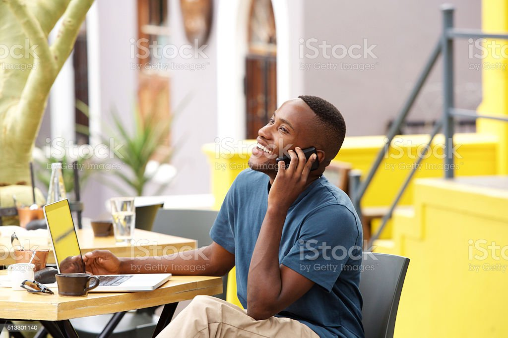 Smiling young african man talking on mobile phone at cafe stock photo