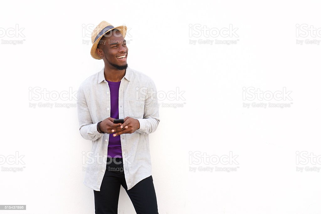 Smiling young african man with a cellphone stock photo