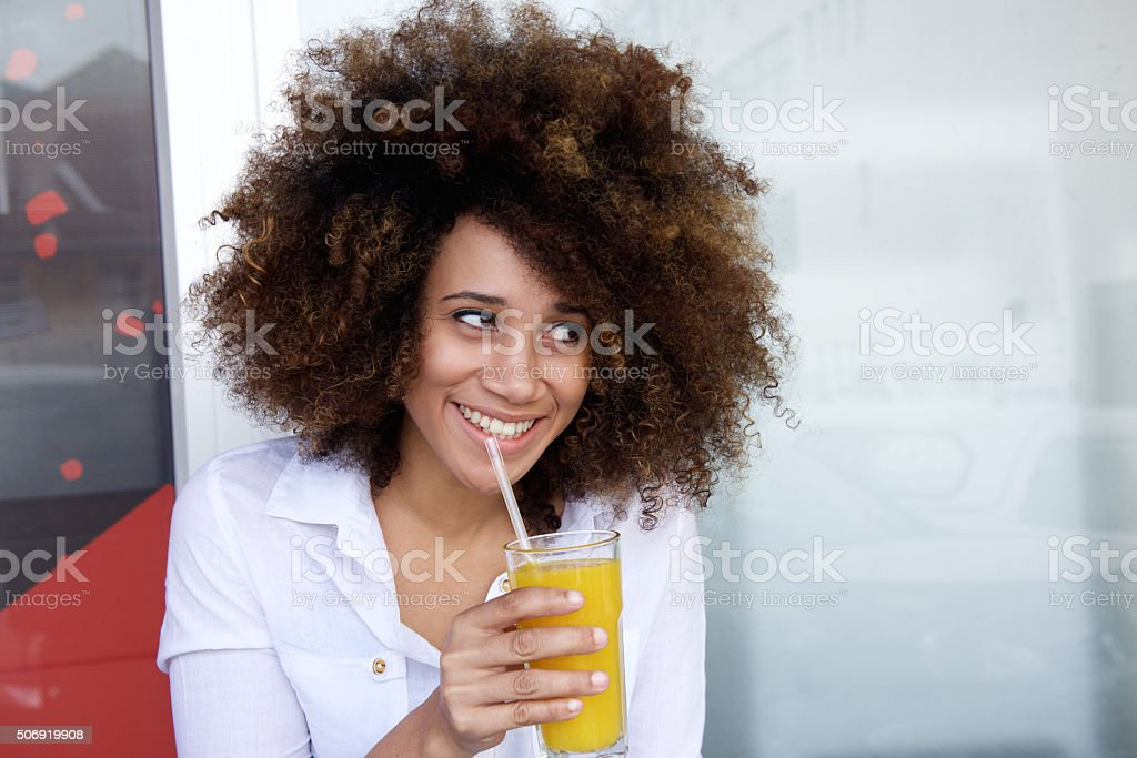 Smiling young african woman drinking juice at outdoor cafe stock photo