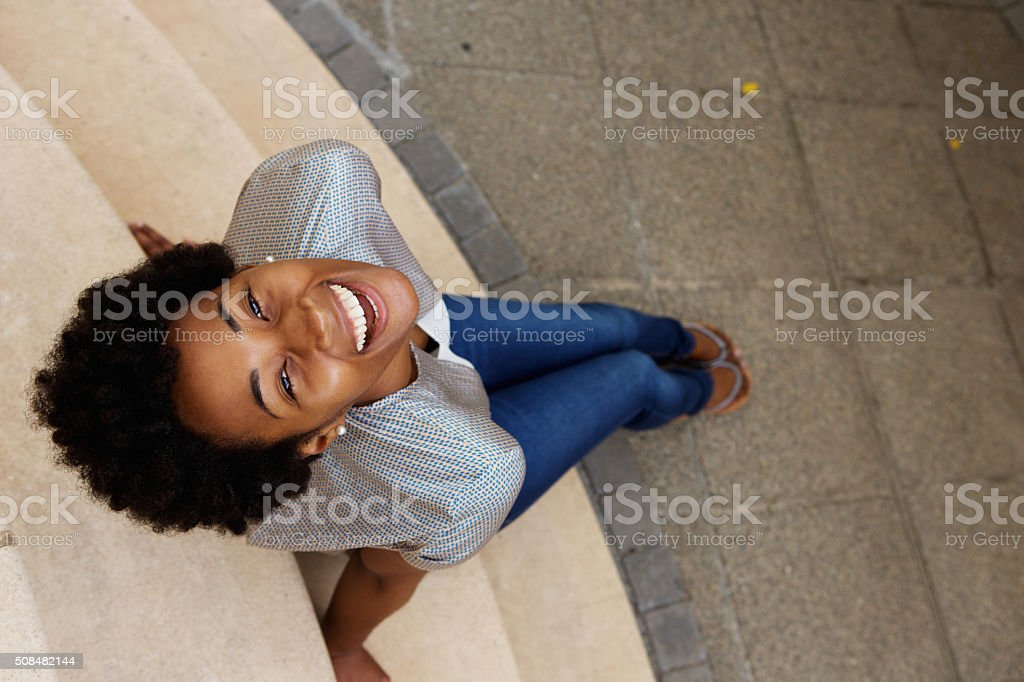 Smiling young african woman sitting on steps and looking up stock photo