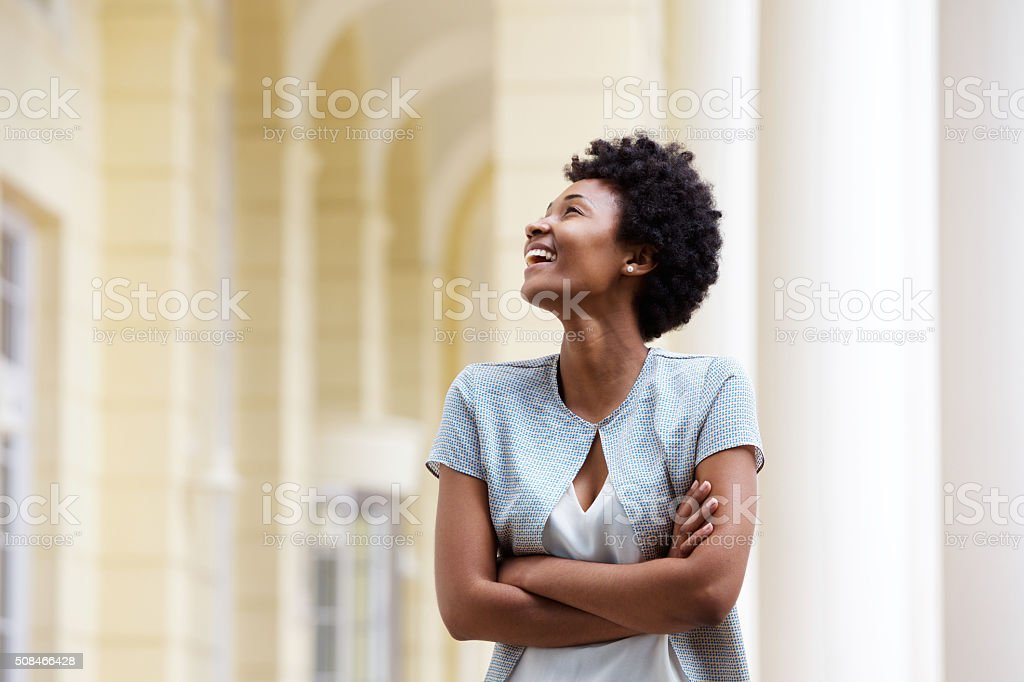 Smiling young african woman standing outdoors stock photo