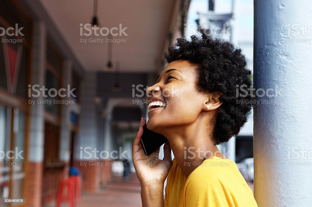 Smiling young african woman talking on mobile phone stock photo