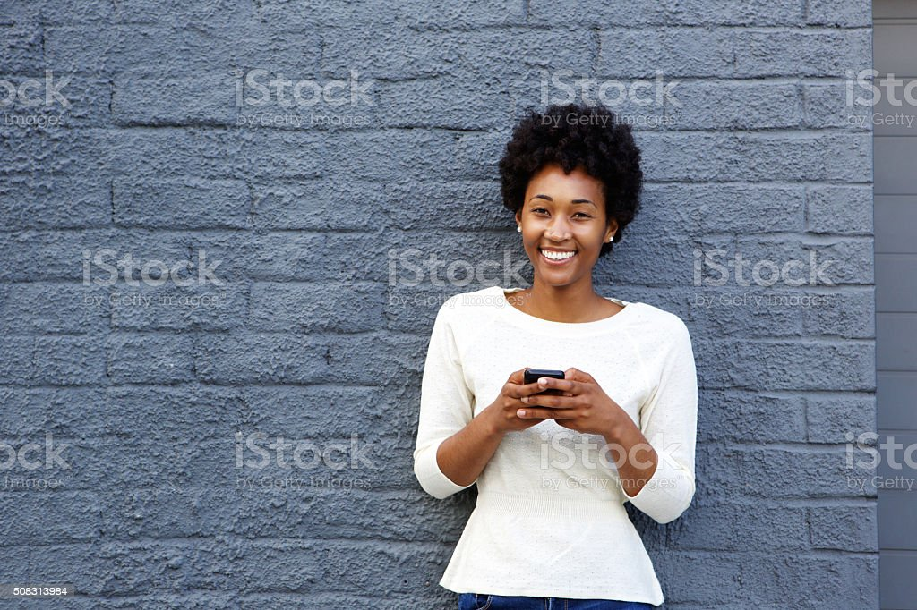 Smiling young african woman with mobile phone stock photo
