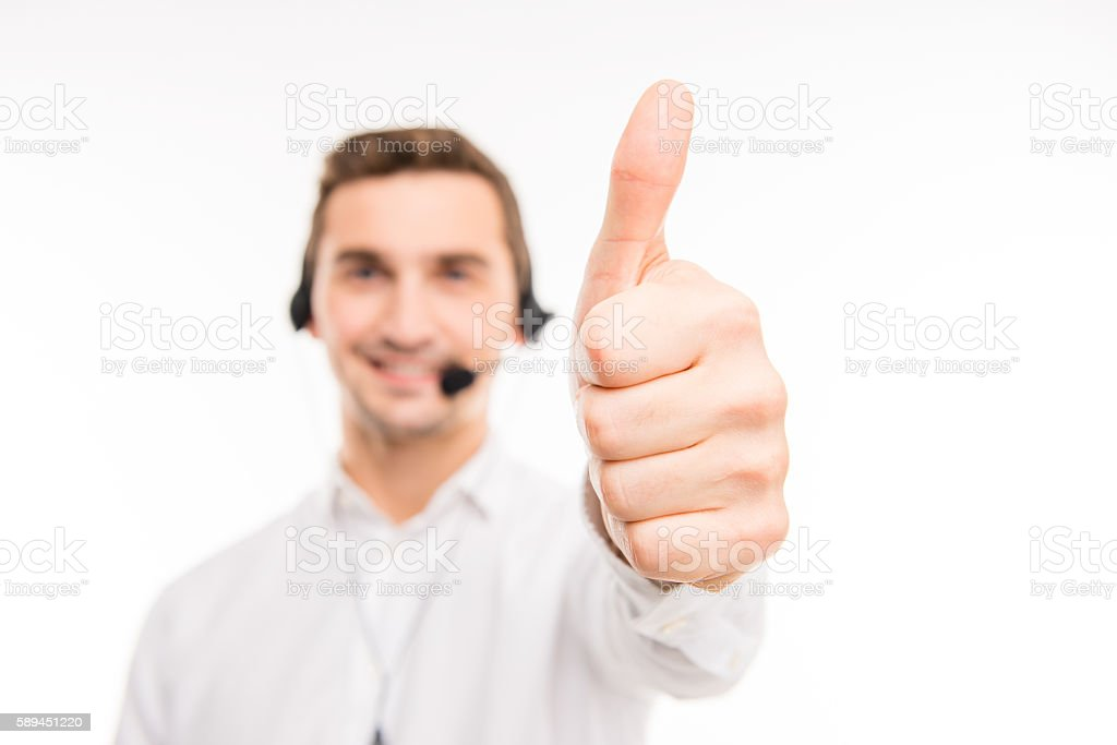 Smiling young agent of call centre showing thumb up stock photo