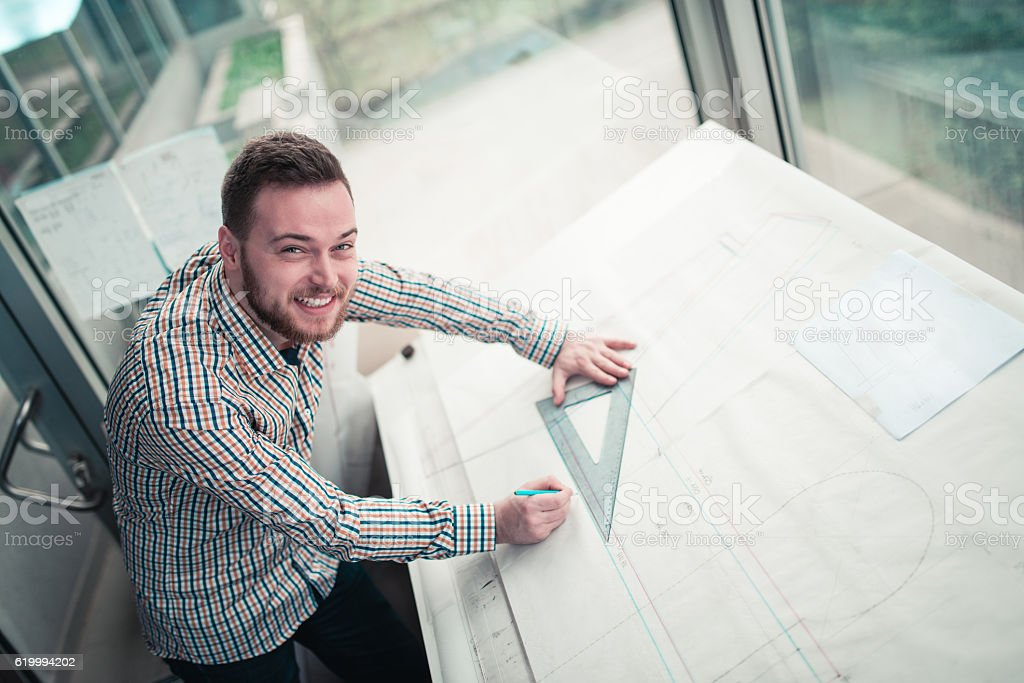 Smiling Young Architect Designer Working Blueprint Plans in His Office stock photo