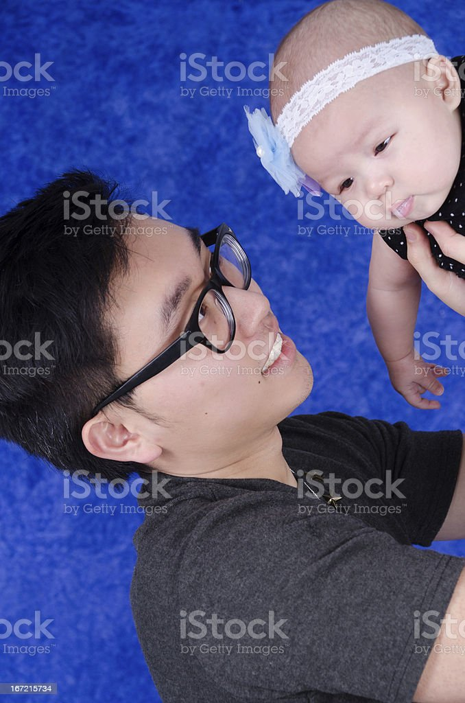 Smiling young Asian father holding daughter above him. royalty-free stock photo