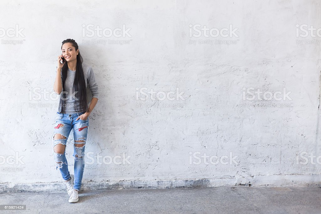 Smiling young asian woman leaning back on blank wall stock photo