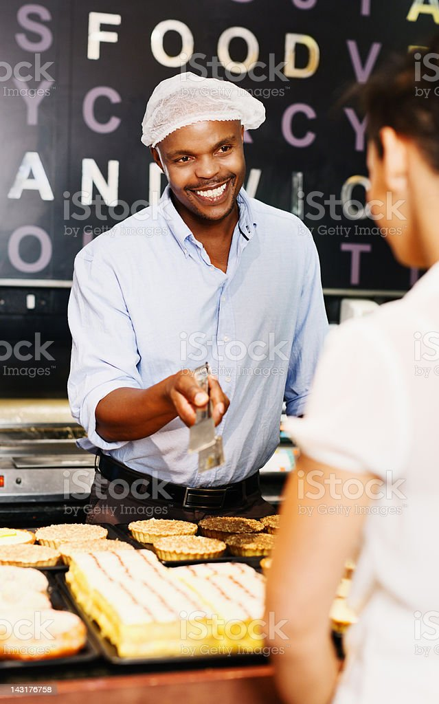 Smiling young baker shows customer some tempting confectionery stock photo