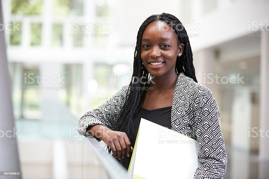 Smiling young black female student in university foyer stock photo