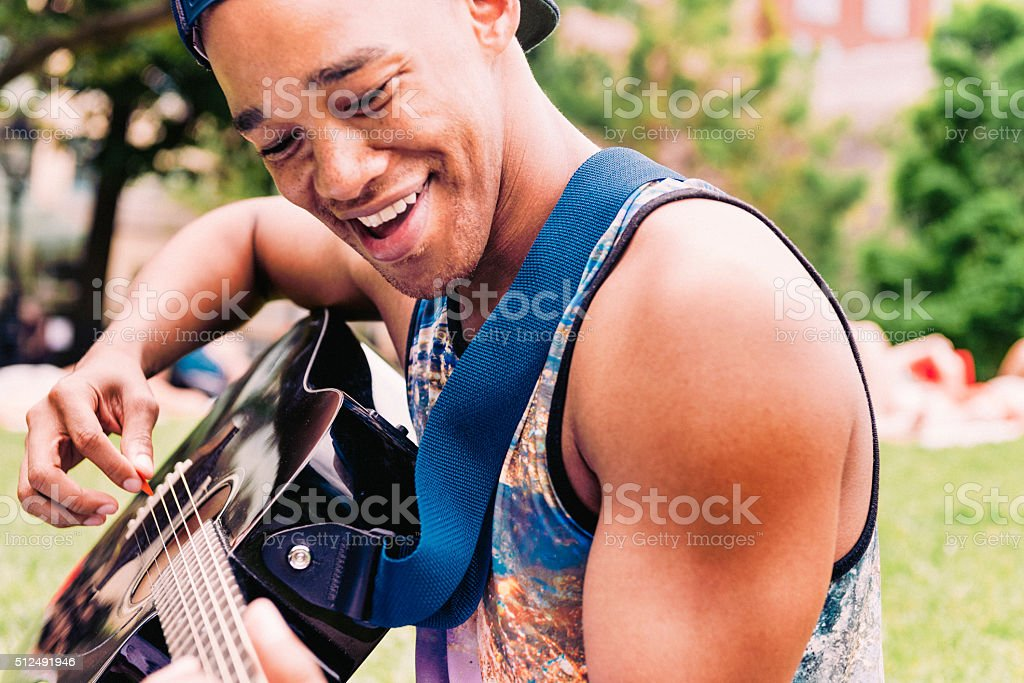 Smiling Young Black Man Playing Acoustic Guitar in NYC Park stock photo