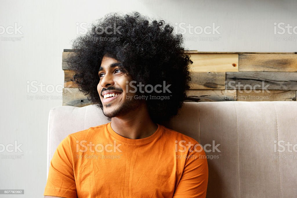 Smiling young black man with afro looking away stock photo