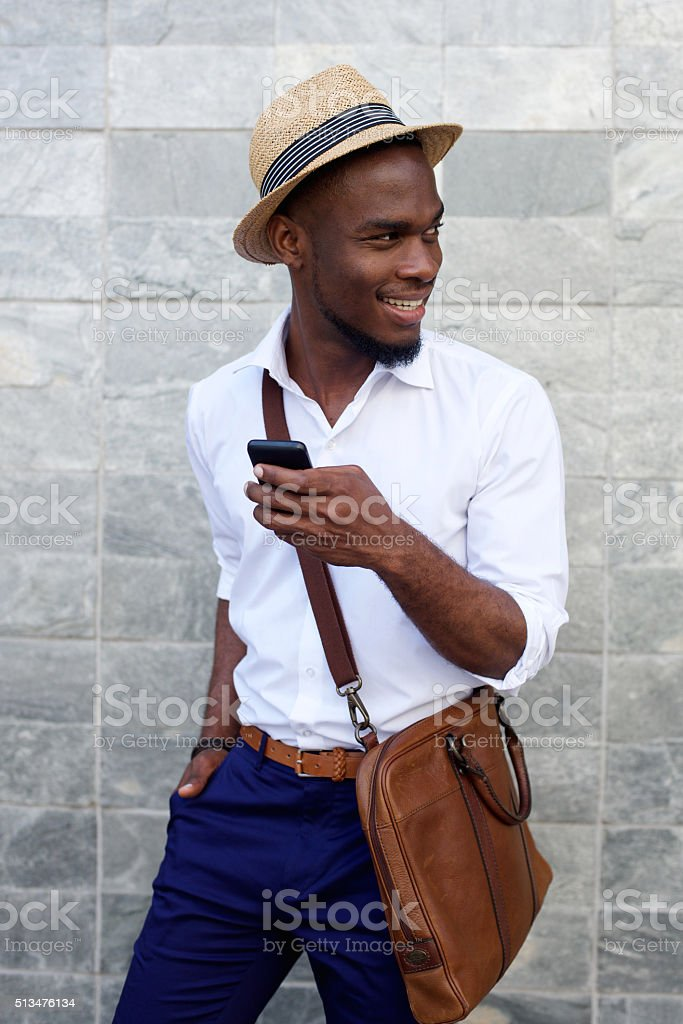 Smiling young black man with mobile phone and bag stock photo
