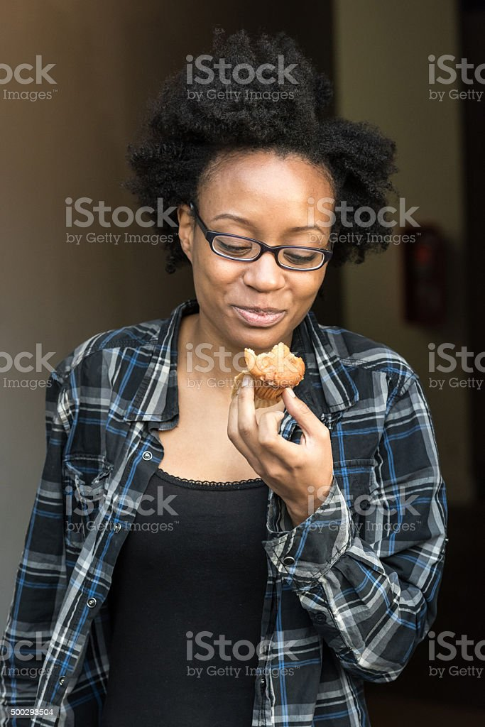 Smiling young black woman having a muffin stock photo