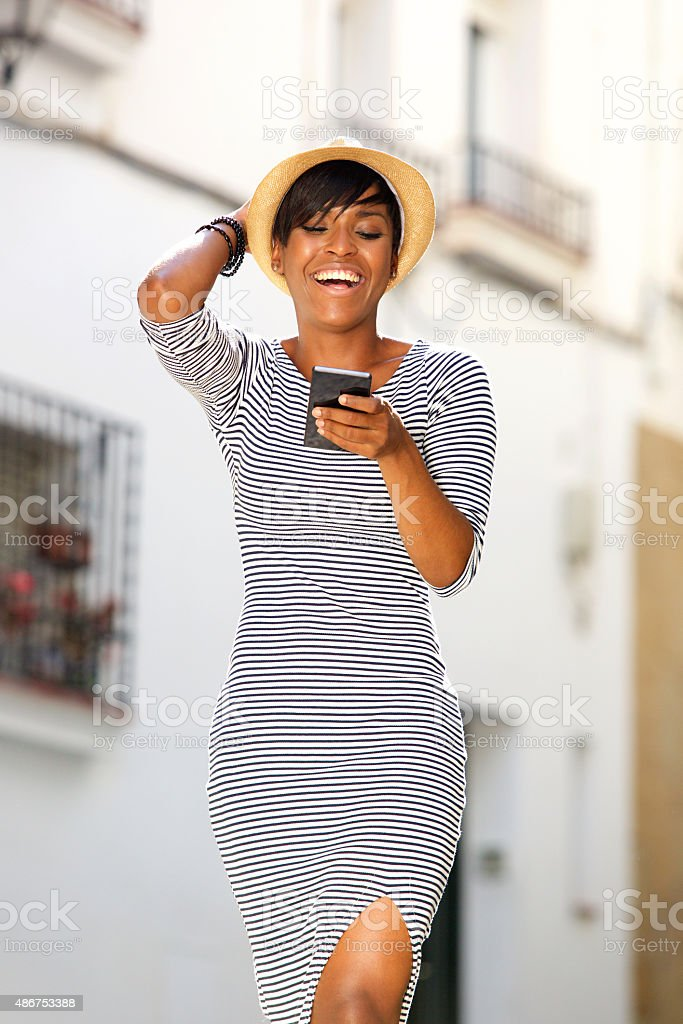 Smiling young black woman reading text message on cell phone stock photo