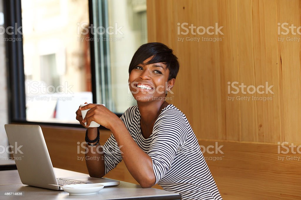 Smiling young black woman with coffee and laptop at cafe stock photo