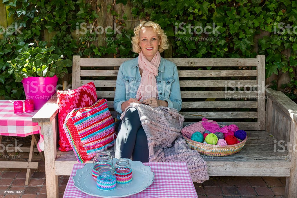 Smiling Young Blond Woman Crochets In The Garden stock photo