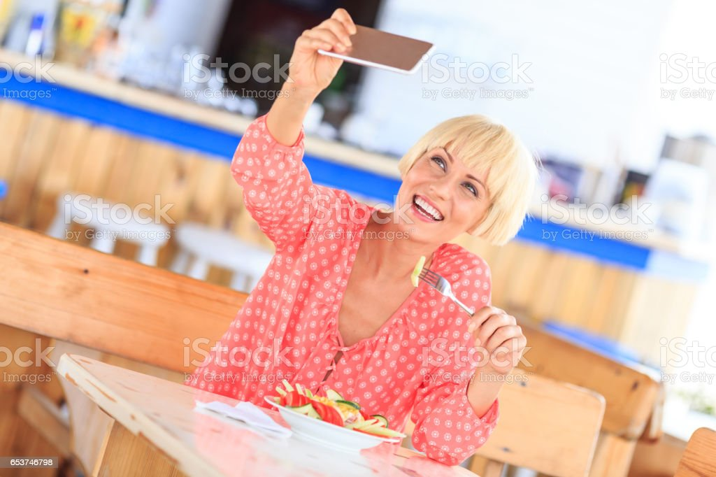 Smiling young blond woman making selfie in restaurant stock photo
