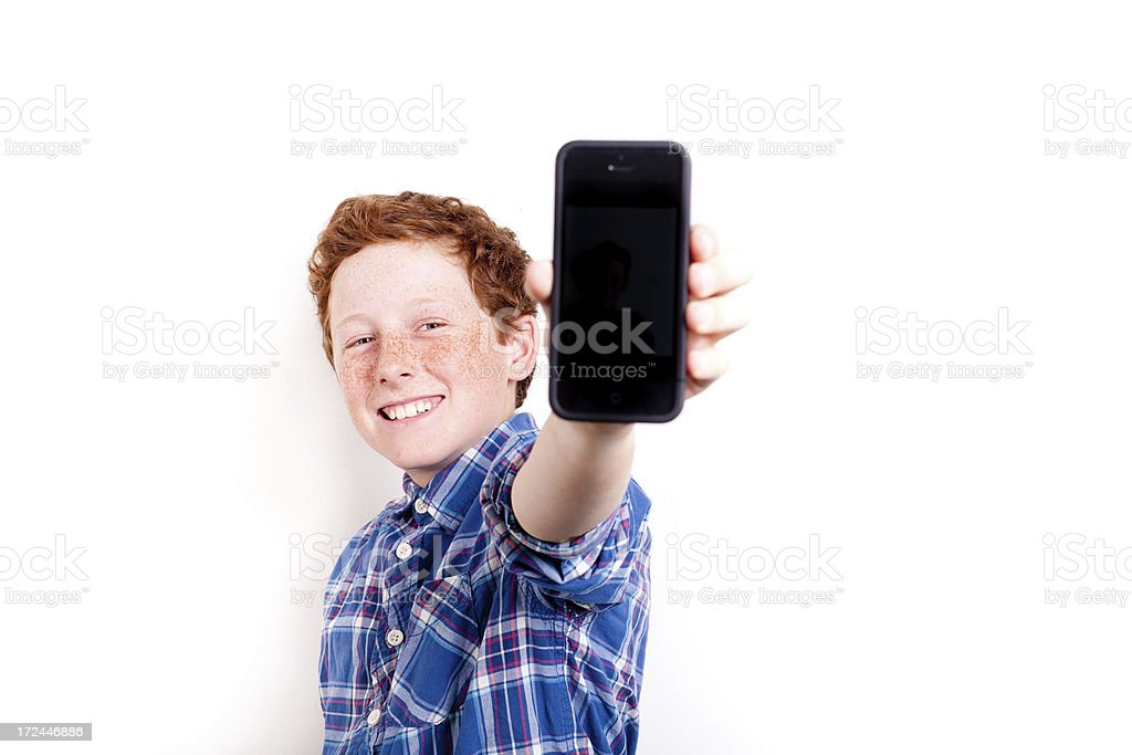 Smiling young boy holding a smartphone royalty-free stock photo