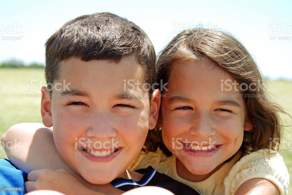 A smiling young brother and sister posing outdoors stock photo