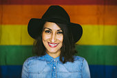 Smiling Young Brunette Girl in Hat Posing On Rainbow Background