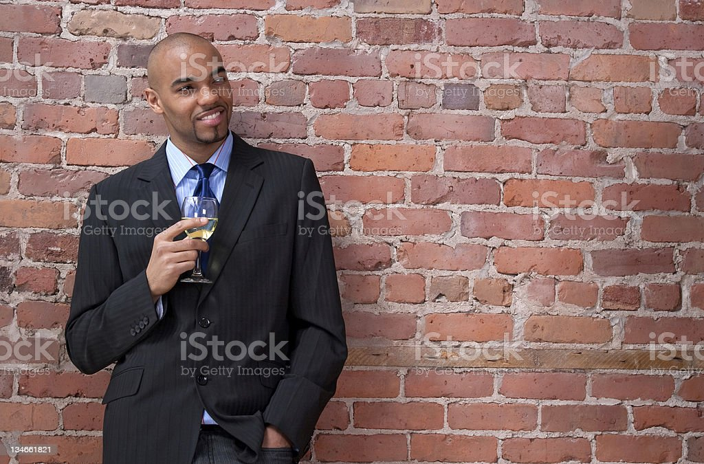 Smiling young business man drinking wine royalty-free stock photo
