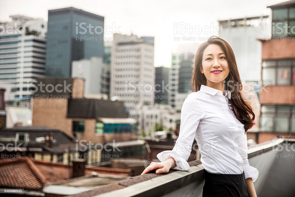 Smiling young business woman in Seoul downtown stock photo