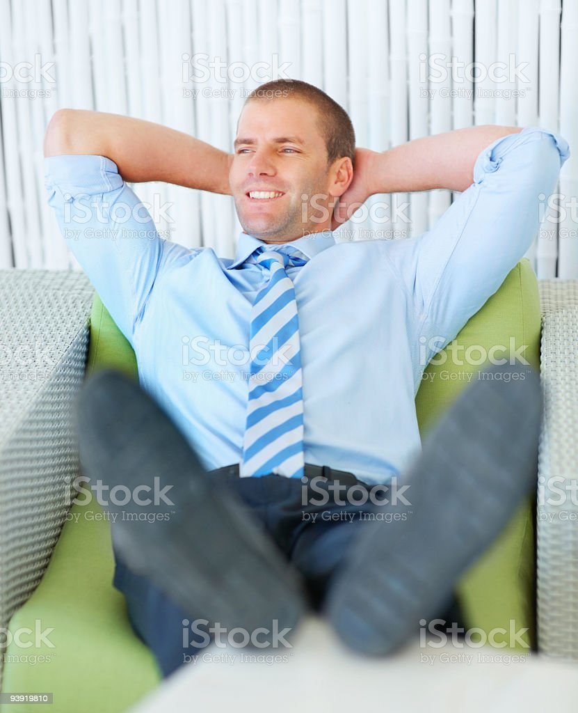 Smiling young businessman lying on couch royalty-free stock photo