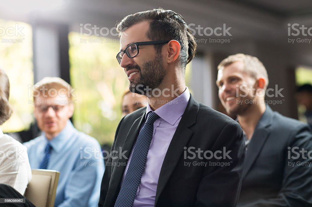 Smiling young businessman sitting at seminar with his colleagues stock photo