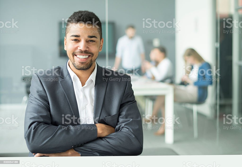 Smiling young businessman sitting in office stock photo