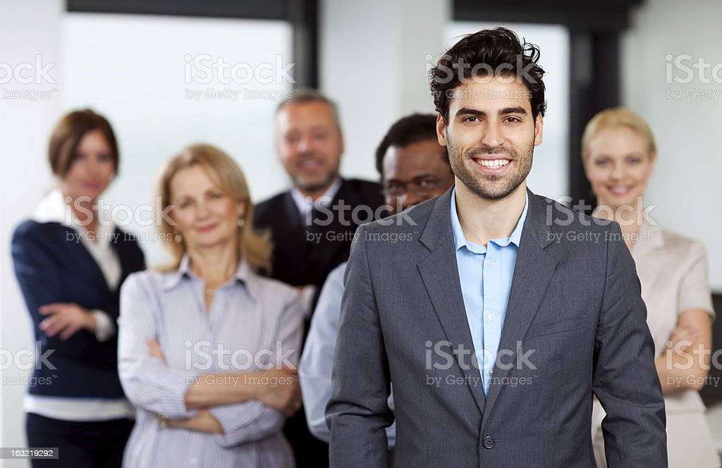 Smiling young businessman with colleagues in background royalty-free stock photo