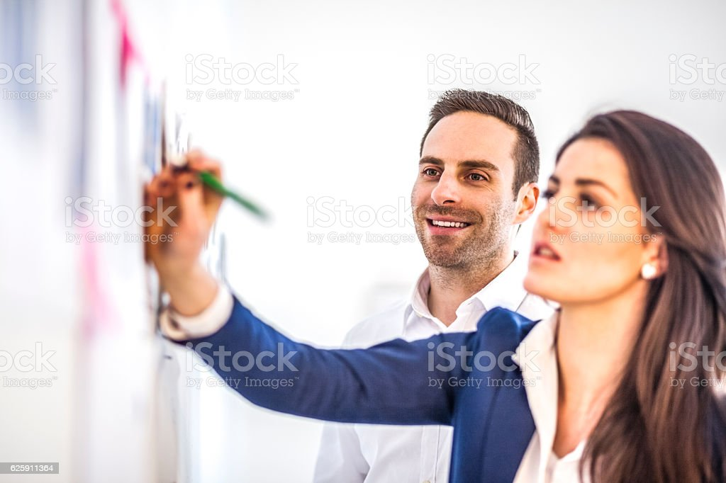 Smiling young businessman with female colleague brainstorming in creative office stock photo